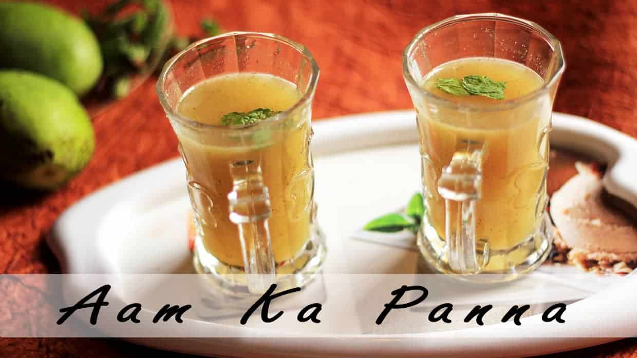 Aam Ka Panna on a transparent glass with some mints leaf keeped on a white tray with some raw mango on the background |