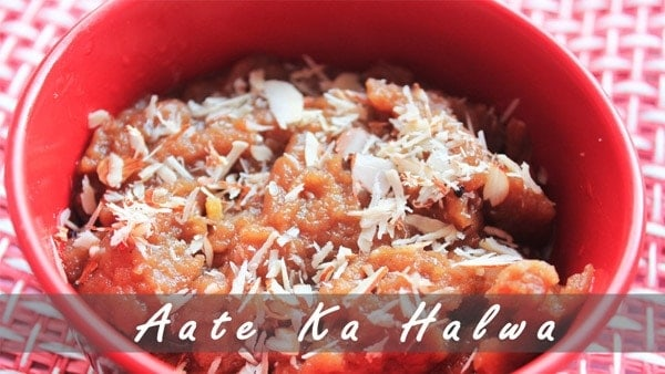 Aate ka halwa on a red bowl with lots of slivers of almond and cashew keeped on a mattress|