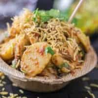 Aloo chaat on a disposable plate garnished with some sev and coriander leaves with a toothpick on a dark mat sprinkles with some sev   www.mintsrecipes.com  