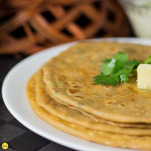 Aloo Parantha   On a white plate with some aloo paratha's kept on a dark color mat and some potato mixture on a white bowl.