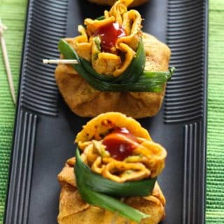 Besan Chilla Potli On a black rectangular tray with some chilla potli on it with some garnishing of spring onion and tomato ketchup kept on a green mattress with some toothpick around it |