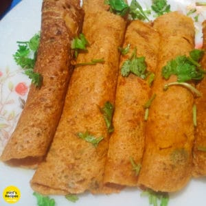 Besan ka chilla on a floural print plate with some garnishing of coriander leaves