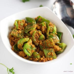 Besan Shimla Mirch on a white bowl full of besan capsicum garnished with some coriander leaves