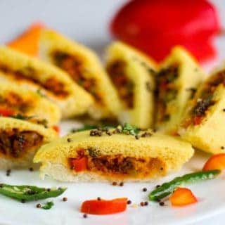 Bread dhokla sandwich on a white plate cutted into pieces in half and tempering of mustard seed and chilli with few strings of curry leaves | www.mintsrecipes.com |