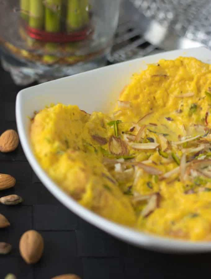 Bread rasmalai on a white bowl garnished with some chopped almonds and pistachios