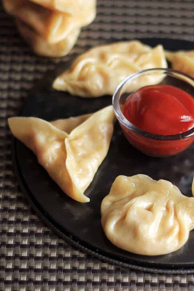 Cheese corn momo on a black round plate with some tomato sauce
