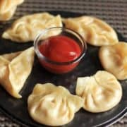 Cheese corn momo on a black round plate with some tomato sauce in the center putted on a dark coloured mat  