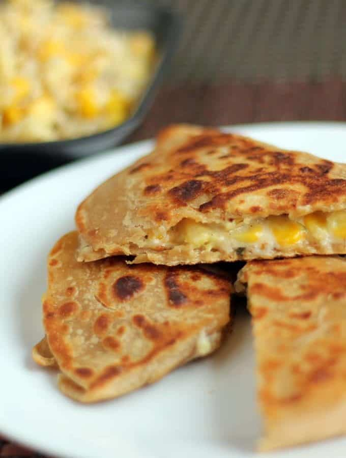 Cheese Corn Pizza Paratha on a white plate with dark background with some cheese corn mixture   www.mintsrecipes.com  