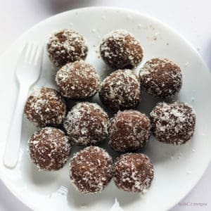 Chocolate coconut balls on a white plate with some coconut balls and garnished with some dessicated coconut