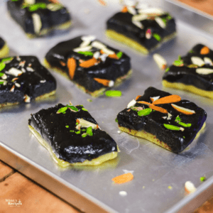 Chocolate Barfi on a steel tray with some pieces of chocolate khoya barfi with some garnishing of pista, and almonds kept on a wooden surface |