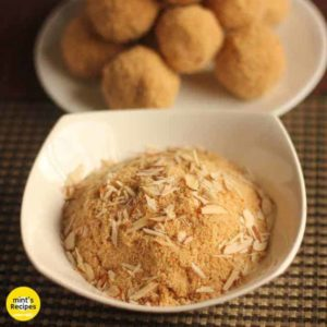 Rajasthani Churma Laddoo on a white plate putted on a mat and a bowl full of churma with some almonds garnished on it  