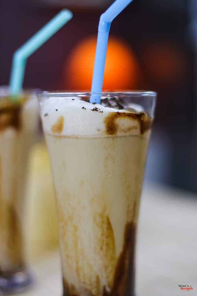 Cold Coffee with Icecream on a glass with some garnishing of chocolate syrup and a strow in it and on the background another glass of coffee ice-cream kept on a wooden surface |