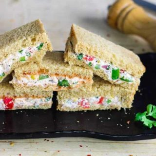 Cream Cheese Sandwich on a black plate for garnishing some coriander leaves and some chilli flakes 