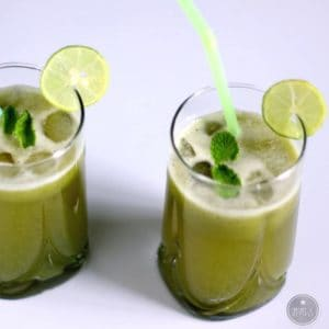 Cucumber Mint Lemonade on a glass with some mints leafs and lemon wedges and a strow in it.It's a very simple and refreshing recipe |