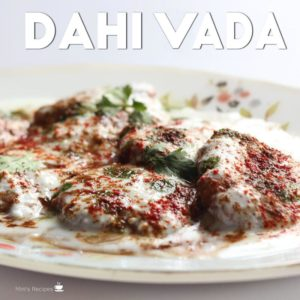 Dahi Vada on a white plate garnished with red chilli powder coriander leaves little chaat masala
