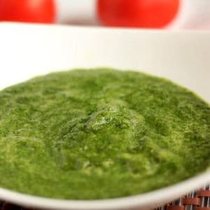 Green chutney dhaniya pudina on a white bowl with some coriander leaves |