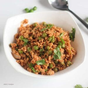 Dry Soya Peas on a white bowl with garnished some coriander leaves on a white background with a spoon |