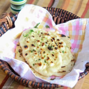 Garlic Naan in a basket with greased butter and garlic mixture some coriander leaves