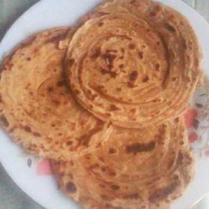 Lacch Paratha recipe | Tasty and soft 3 pcs of laccha paratha on a white flower printed plate kept on a white marble surface |