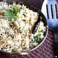 Jeera Rice on a deep vessel garnish with some cilantro on a dark colour mat  