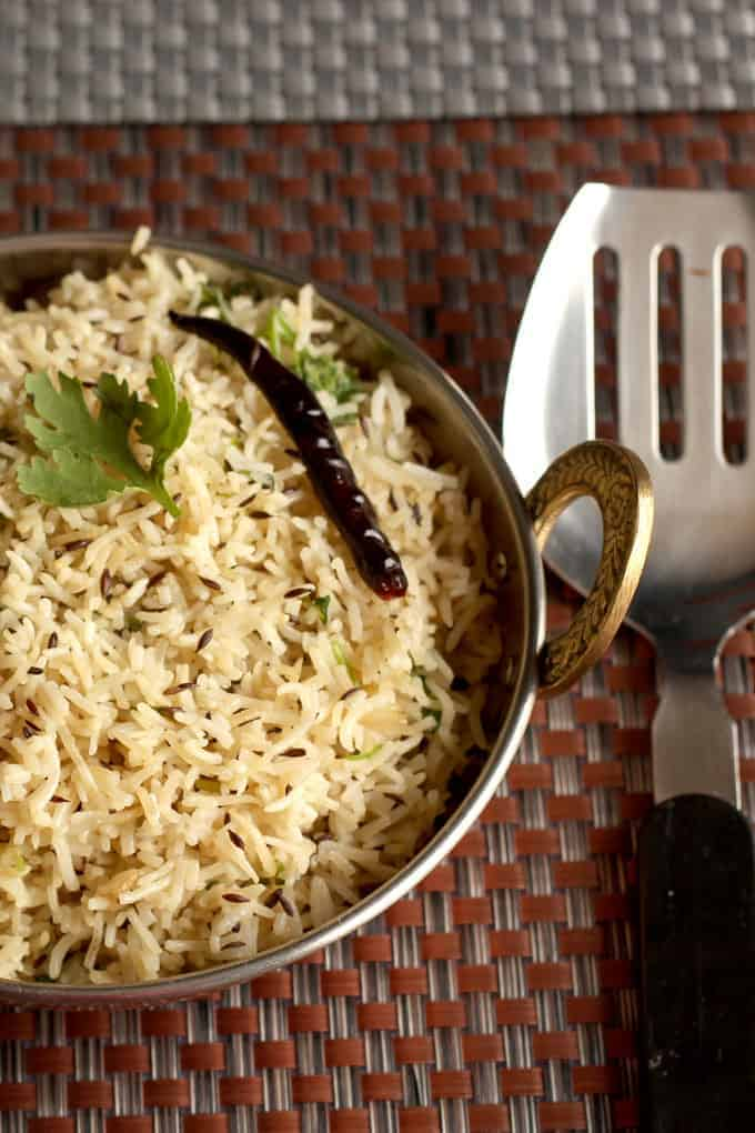 Fried jeera rice in a heavy vessel putted on a dark mat with some garnishing of coriander leaves and fried red chilli on it|