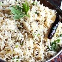 Jeera Rice on a deep vessel garnish with some cilantro on a dark colour mat | www.mintsrecipes.com |