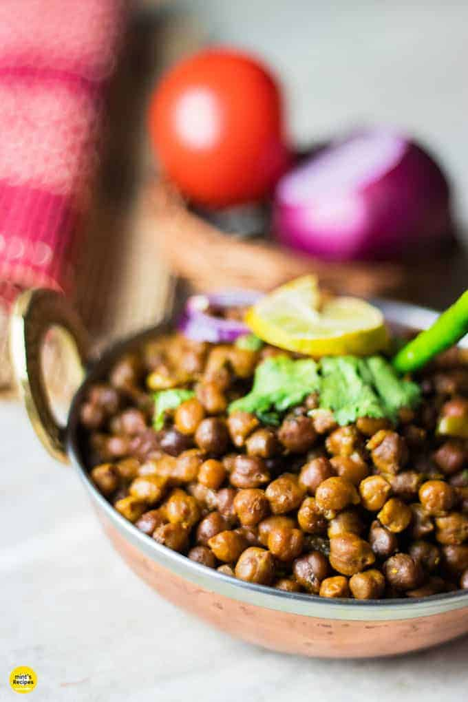 Dry kala chana on a deep vessel with coriander leaves and green chilli on top with a slice of lemon and some onion rings and light background with onion and tomato in a basket.