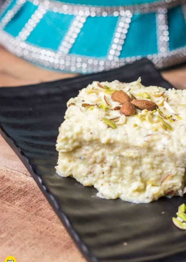 Kesaria Shahi Sandwich on a black tray with some garnishing of pista, almonds and cashew kept on a wooden surface with a basket in the background