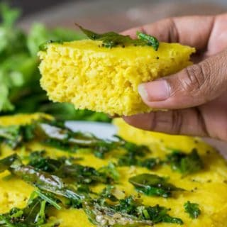 Instant Khaman Dhokla on a dark surface with tempering of mustard seed, curry leaves and chilli |