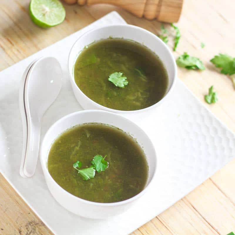 Lemon Coriander Soup on a white bowl kept on a black tray with a spoon and lemon slice and garnished with coriander leaves  