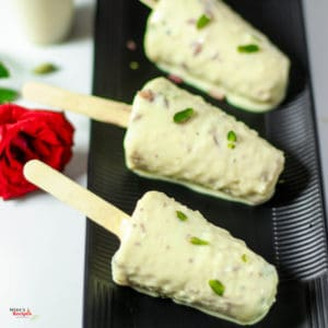 Malai kulfi stick on a black plate, kulfi coated with pista on a white light background with a red rose on the backside of the plate Roti noodles on a white bowl full with roti noodles and garnished with coriander leaves with a light background