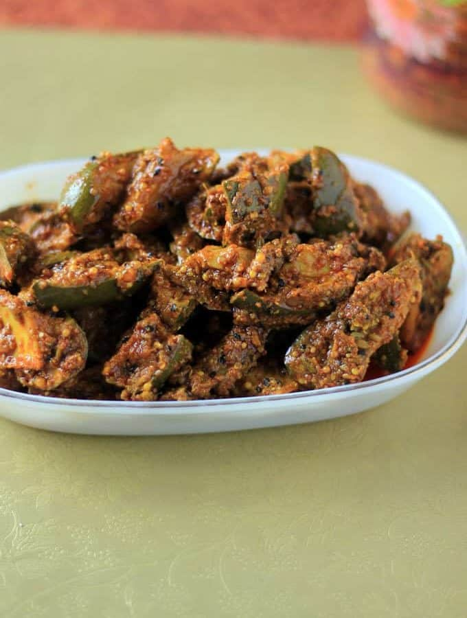 Mango Pickle on a white plate on a green surface |