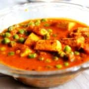 Matar Paneer on a transparent plate on a white surface |