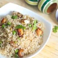 Matar paneer pulao in a white bowl with some coriander leaves kept on a wooden surface with top wooden bowls in the background |