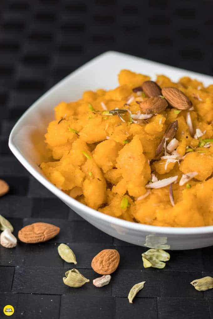 Moongdal ka halwa on a yellow bowl garnished with almonds