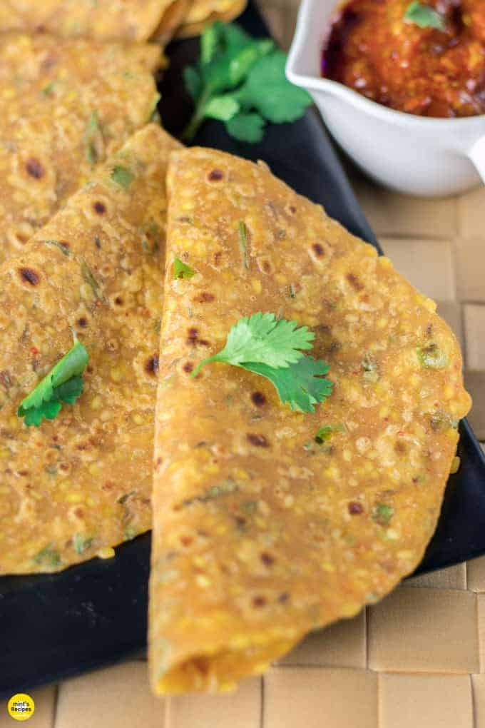 Sabut moongdal ka paratha on a black tray with some coriander leaves and some pickles on the background