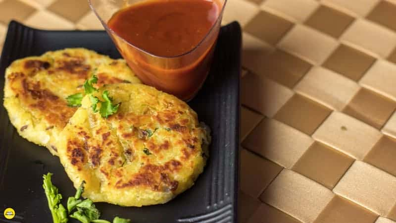 Moong dal ki tikki on a black tray with some moongdal tikki and garnished with some coriander leaves, kept on a brown colored mattress