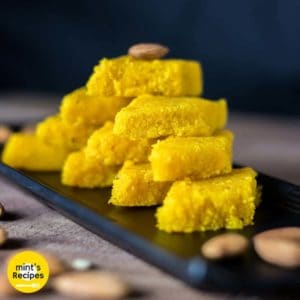 Nariyal ki barfi on a black plate with some almonds and pictachios on a wooden surface |