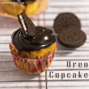 Oreo Cupcake on a steel rods with frosting of chocolate ganache and half oreo biscuits on it and some oreo cupcakes on the background |