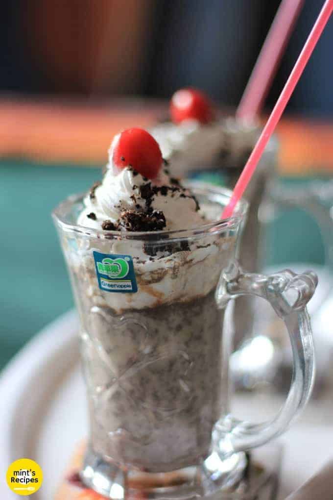 Oreo-Milk-Shake on a white surface with 2 glasses of milkshake decorated with some heavy cream with some oreo biscuit crush and a cherry on the top with a strow in it |