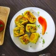 Paneer Bhurji Swiss Roll on a white plate with some swiss rolls and tomato ketchup spread on one side, garnished with spring onion and a small bowl of tomato ketchup on the background