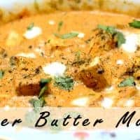 Paneer butter masala on a floural printed plate garnished with some fresh cream and coriander leaves |