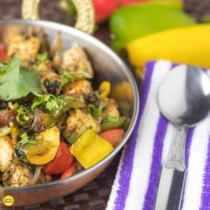 paneer capsicum masala on a deep vessel garnished with some coriander leaves on a dark mat with some yellow and red bell peppers and green capsicum with a spoon on a handkerchief |