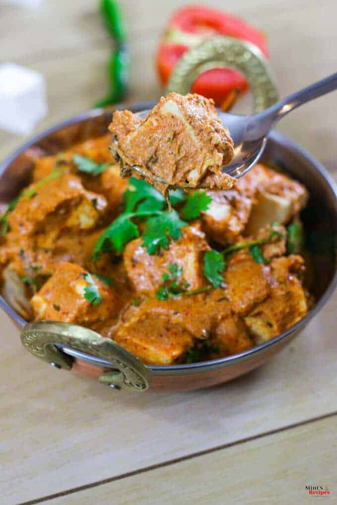Paneer Makhni on a deep vessel kept on a wooden surface with garnishing of coriander leaves and a spoon kept beside it and some tomato slices, chili and paneer cubes on the background |