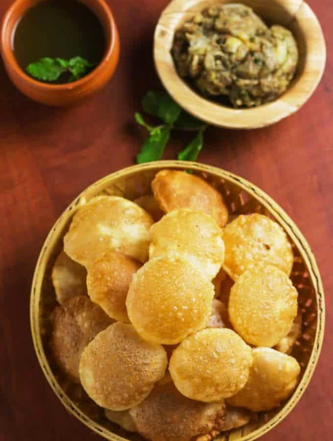Pani Puri on a wooden basket full of puri's and potato mixture on a wooden plate and some sour water in a clay pot with some coriander leaves in it |