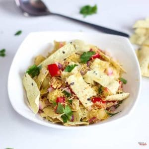 Papad Bhel on a white plate with some papad bhel with little sev sprinkles on it and garnished with some coriander leaves and some roasted papad on the background kept on a white surface |