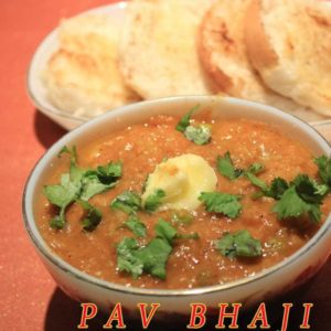 Indian Pav Bhaaji on a white surface wit for pav pieces on a white tray and a bowl full of bhaji with little butter and garnished with some coriander leaves and a spoon,fork in both side oh pav bhaji |