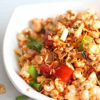 Popcorn Bhel on a white bowl with lots of veggies and popcorn mixture with some garam masala and sev for garnish.|