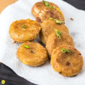Potato Cheese Corn Rolls| Potato cheese corn rolls on a white plate with an absorbing paper and some coriander leaves to garnish |