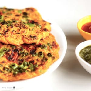 Potato Lachcha Pancake on a white plate with some pancakes on it and garnished with some coriander leaves